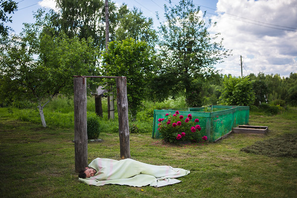 Producer and photographer Mikhail Mordasov naps outside Elizaveta Andreyevna's home.