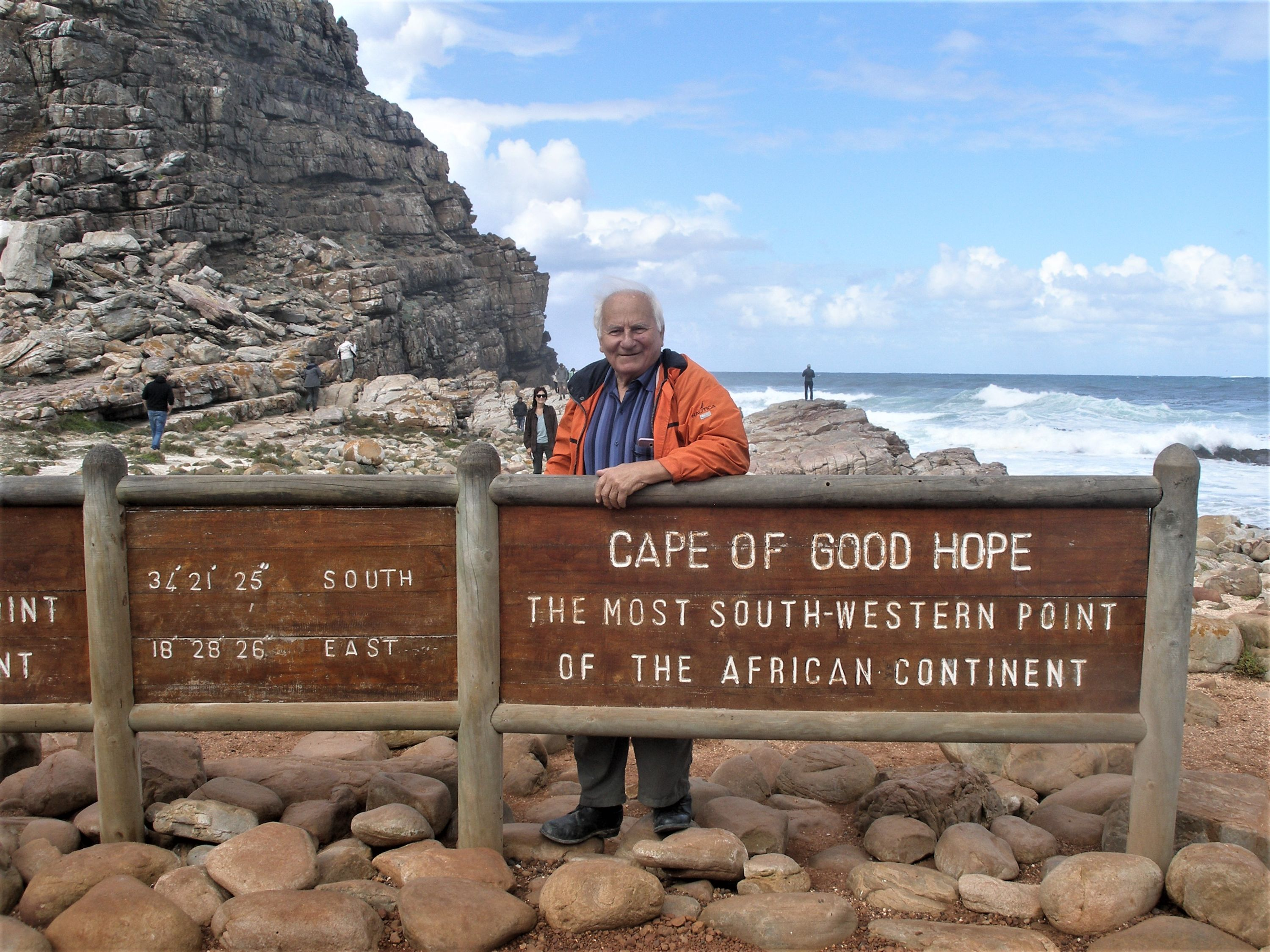 Man standing at Cape of Good Hope sign.