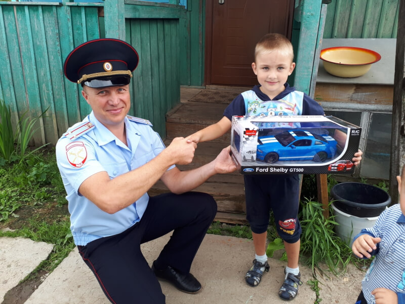 Russian police officer gifts a child a toy car